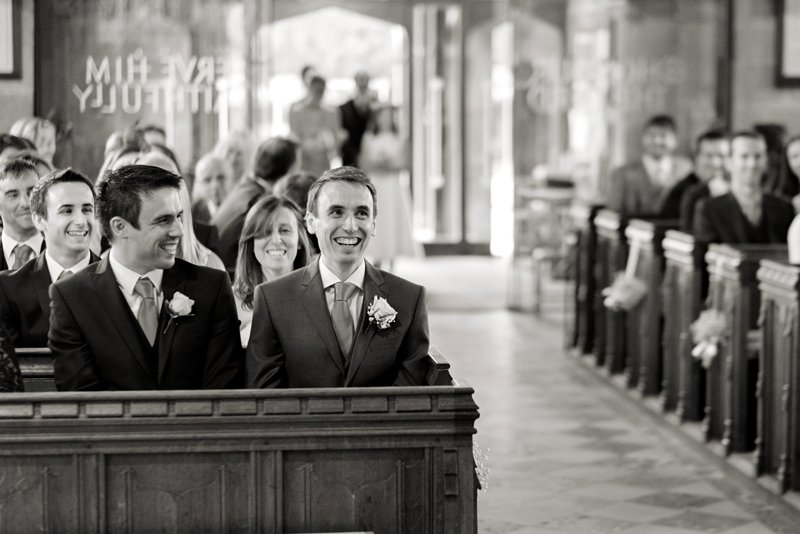 Black and white wedding photographs. A groom awaits his bride at St Alkmund's Church, Duffield, Derbyshire.