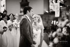 Black and white wedding photograph of exchange of vows in Sheffield church