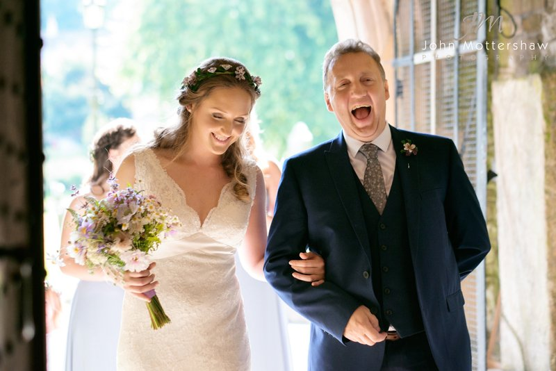 Bride with father laughing as they enter church