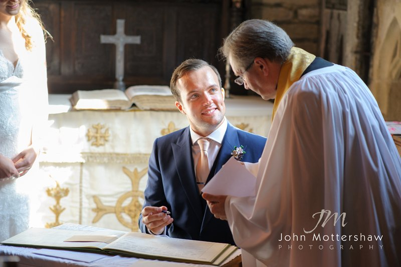 groom signing the register at Taddington Church, Buxton