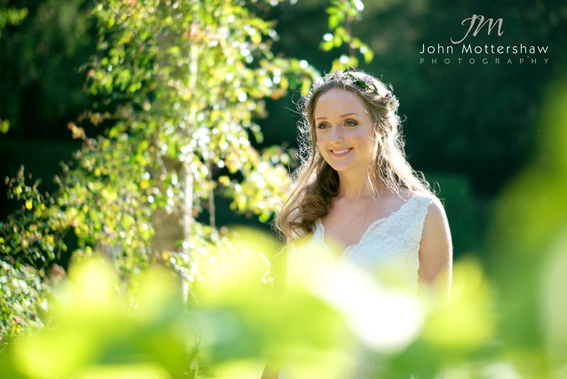 A bride enjoys the evening sunshine at Hassop Hall