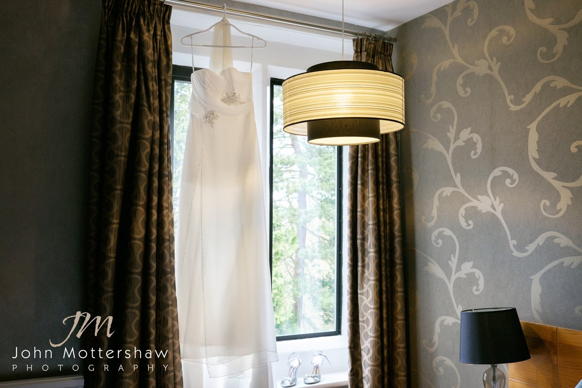 The wedding dress hangs ready in hotel room