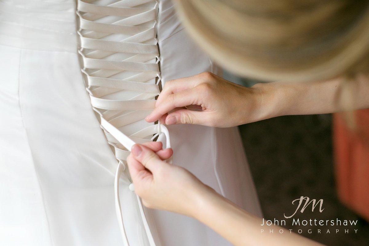 bridesmaid ties up the bride's dress. The Maynard