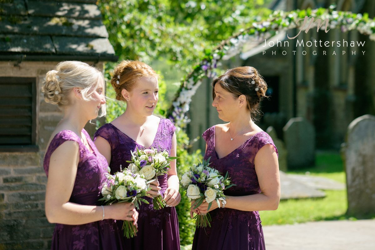 Bridesmaids await the bride at Taxall Church in Cheshire