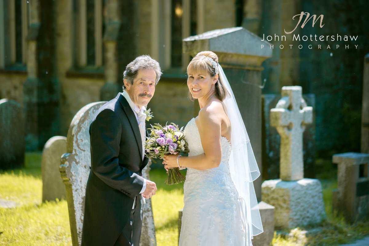 Wedding photographer captures the bride and her father walking to church in Cheshire