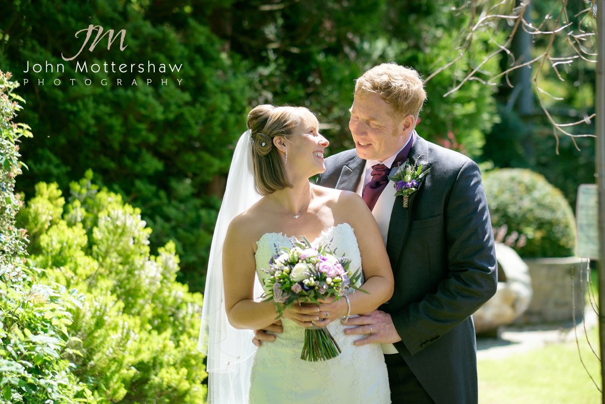bride and groom pose at a spring wedding in Cheshire