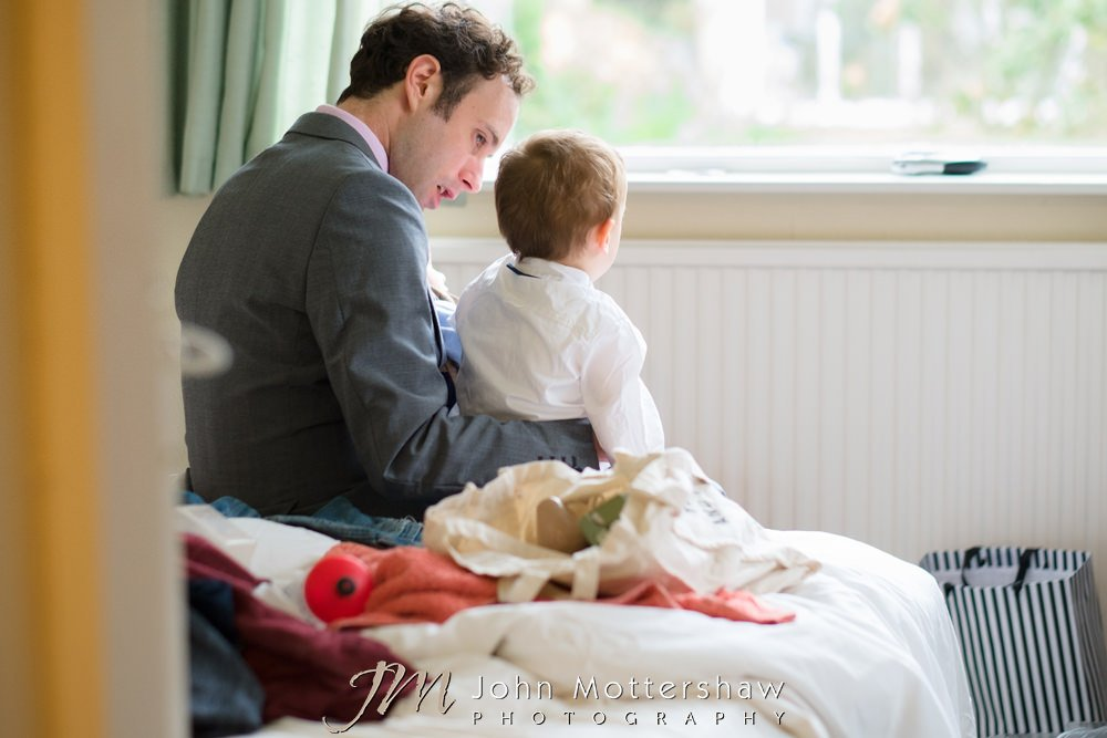 Groom and baby son having a chat before an Old Hall Buxton wedding