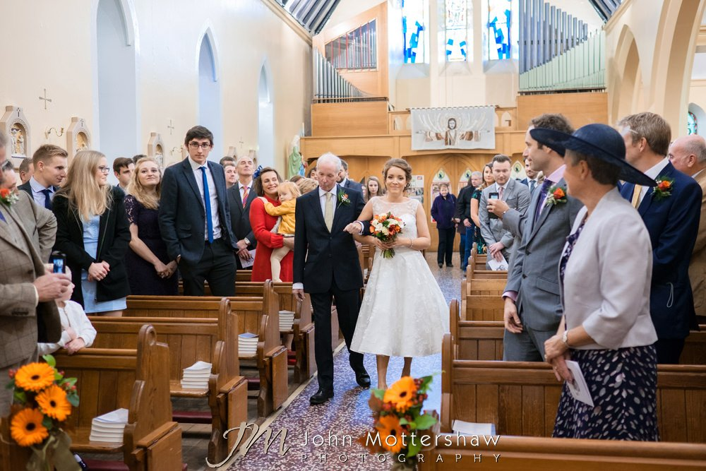 Bride and dad walking down the aisle at St Anne's Church in Buxton