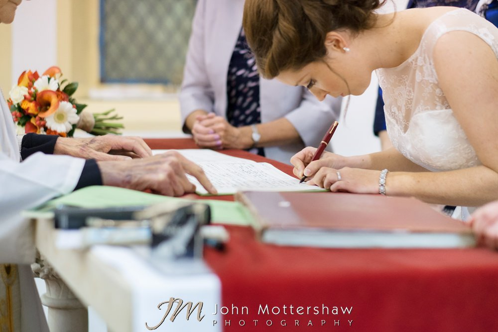 Bride signing the wedding register