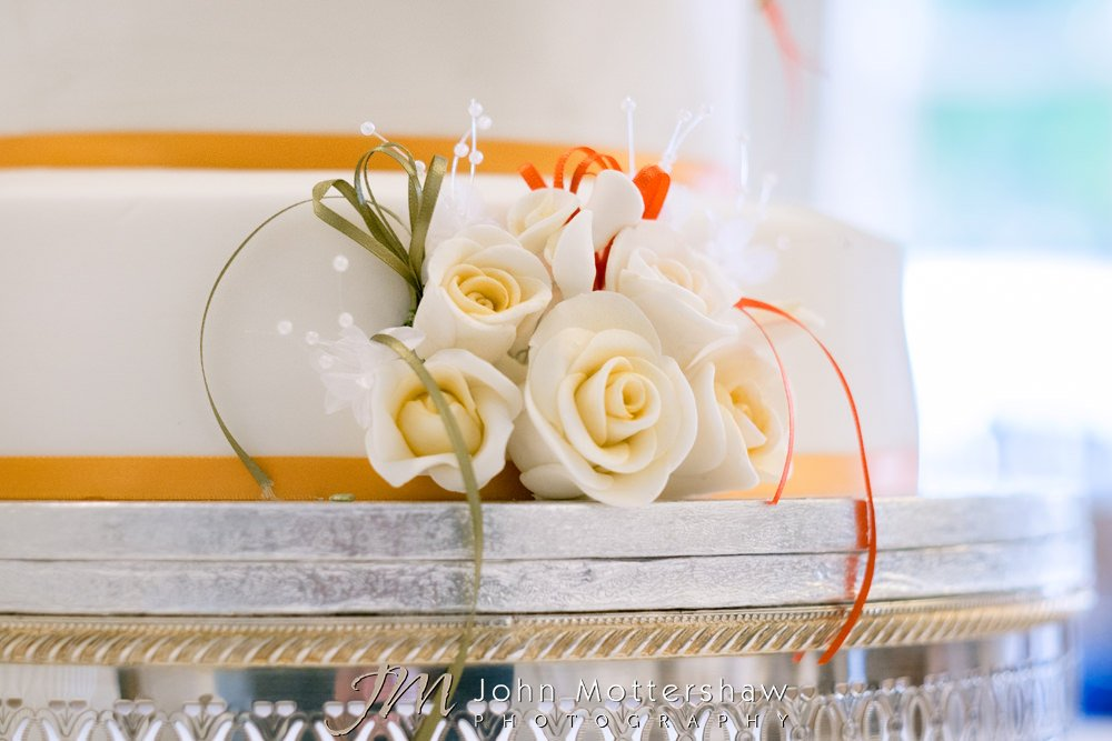 Icing white roses on wedding cake