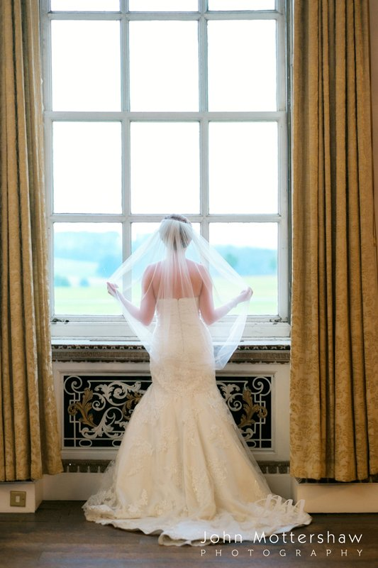 Bride at the window holding veil