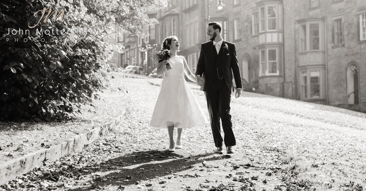 Photograph of a bride and groom walking to the Old Hall Hotel in Buxton, Derbyshire for their wedding reception