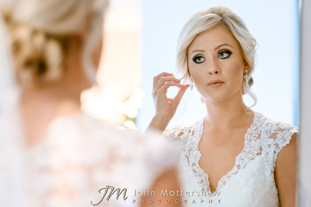 Bridal preparations - bride looking in the mirror
