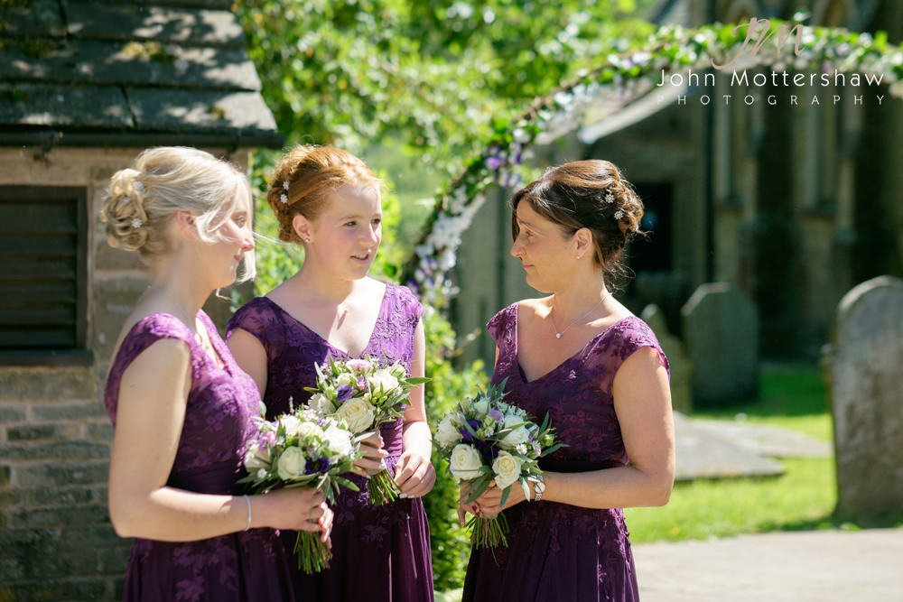 Bridesmaids chat excitedly as they await the bride at a church wedding at Taxal Church.