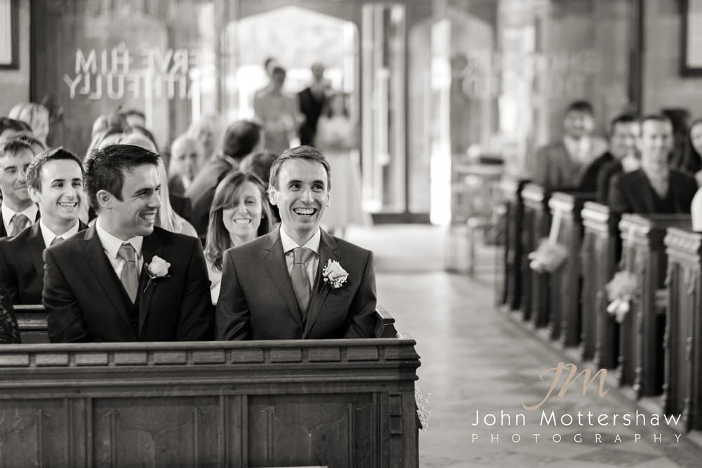 Wedding photograph of a groom at a Derbyshire church wedding awaiting the arrival of his bride.