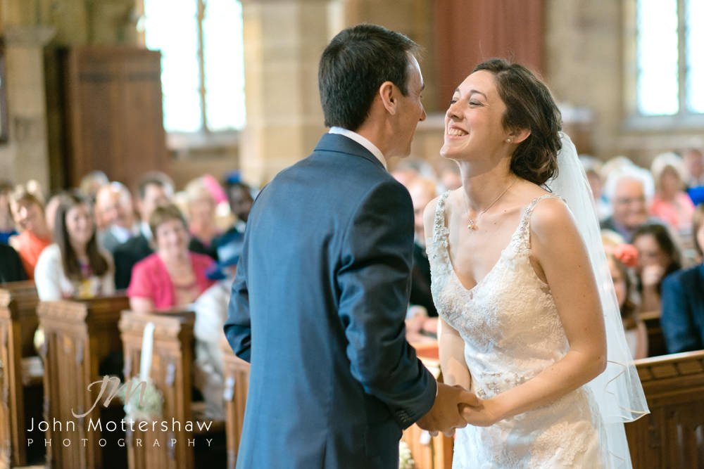 A bride and groom laugh during their church wedding ceremony before their reception at Repton School.