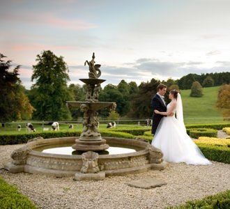A bide and groom pose in the evening sunlight at Hassop Hall. Photography by Sheffield wedding photographer John Mottershaw.