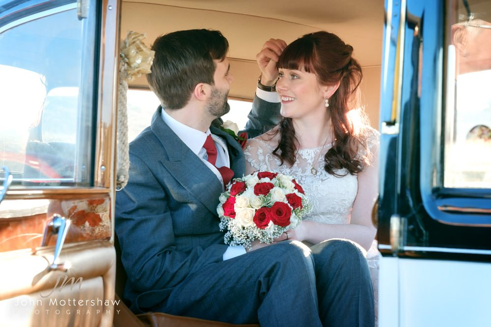 Bride and groom arrive in a vintage car at the Maynard in Grindleford, near Sheffield.