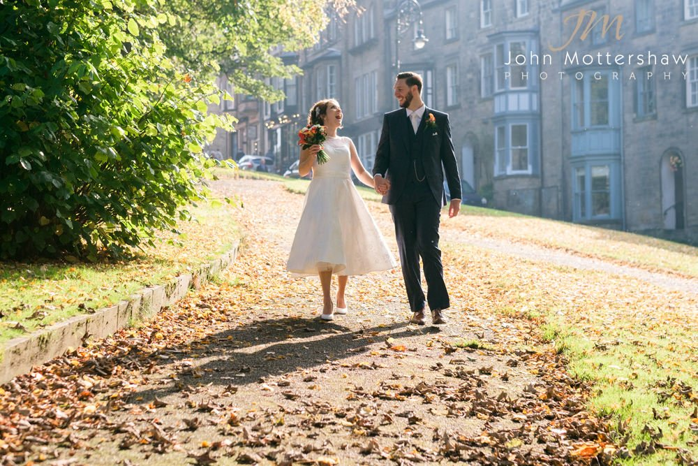 Wedding photograph of a bride and groom walking through Buxton in Derbyshire in beautiful sunshine.