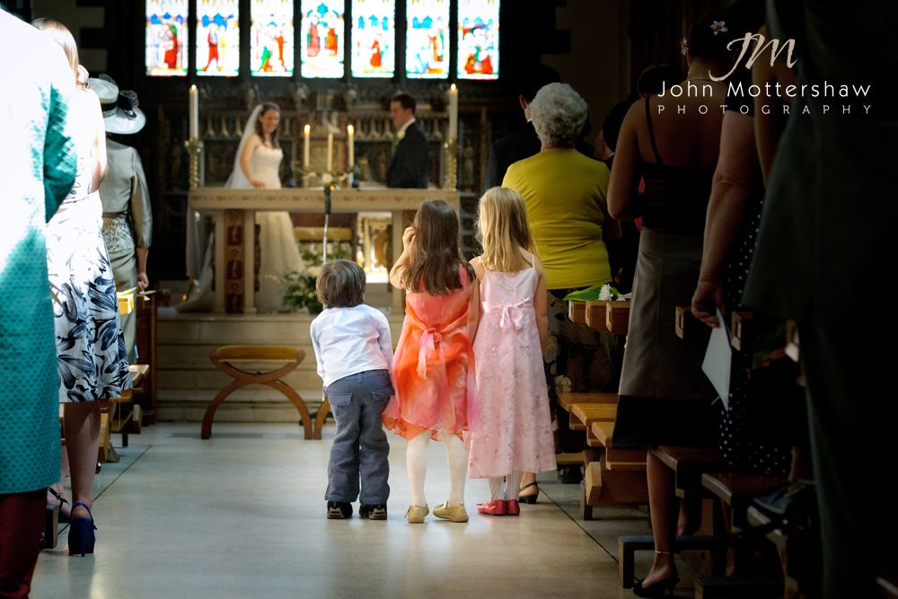 Children look watch the bride and groom during a wedding at Saint Marie's Church in Sheffield.