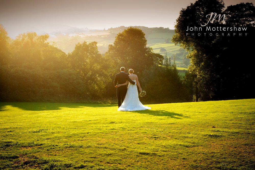 Romantic wedding photograph of a bride and groom walking into the sunset.
