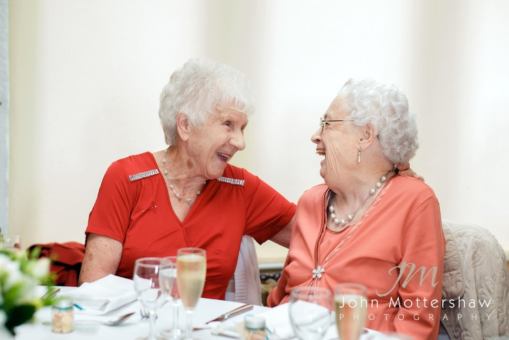 Two ladies laugh at a wedding at The Maynard. Photograph by Sheffield wedding photographer John Mottershaw.