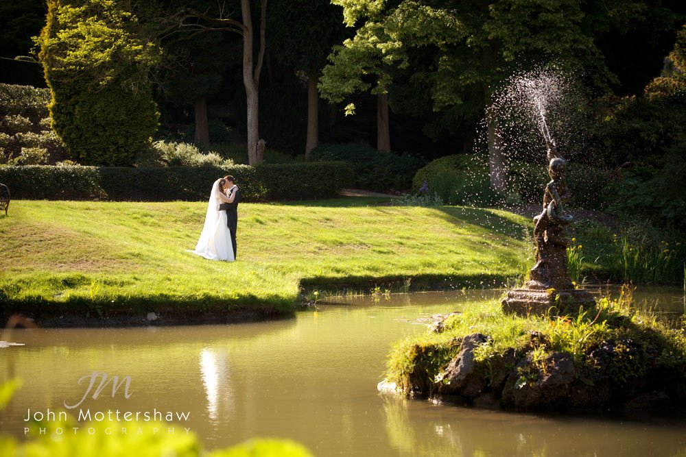 a bride and groom pose for wedding photographs by the lake at Thornbridge Hall near Sheffield.