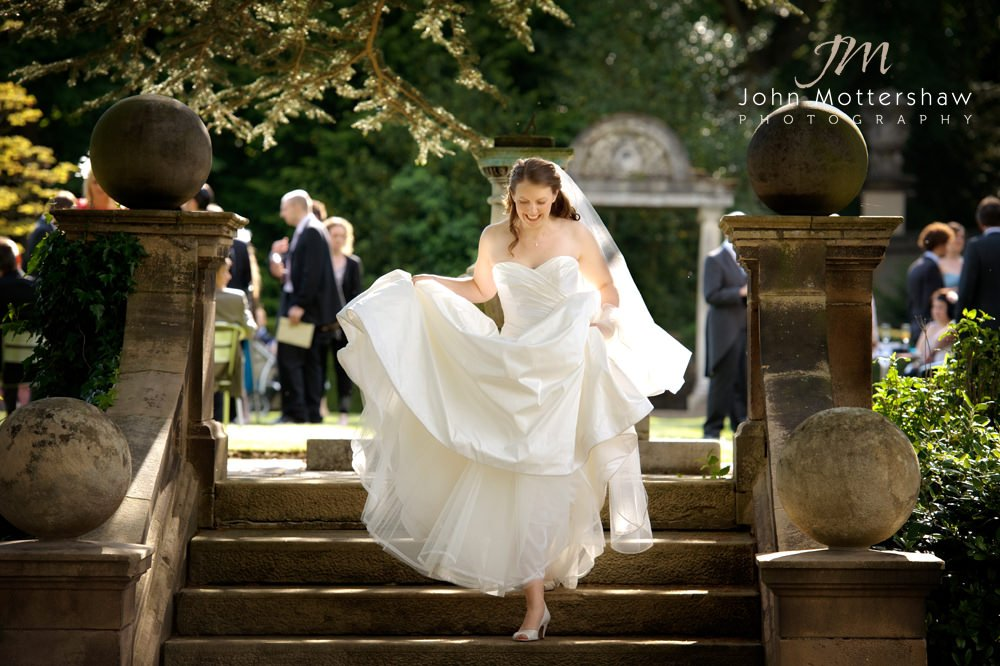 A bride walks down the steps showing her beautiful dress at her summer wedding at Thornbridge Hall near Sheffield.