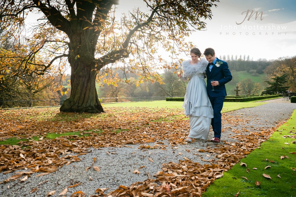 A wedding couple walk along a path at their autumn wedding at Hassop Hall in Derbyshire.