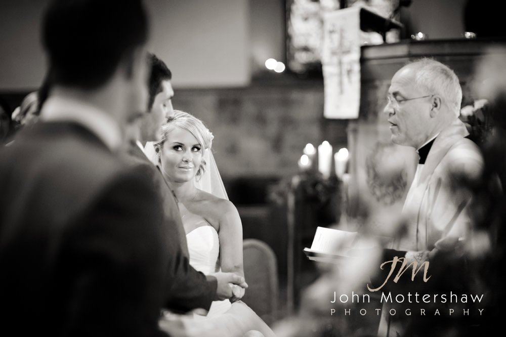A couple exchange vows in Bakewell Church in Derbyshire. The wedding reception was at Hassop Hall.