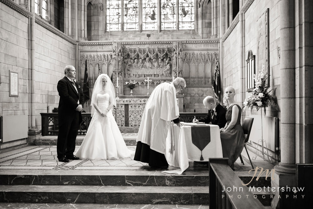 A black and white wedding photograph of a couple signing the register at Wentworth Church.