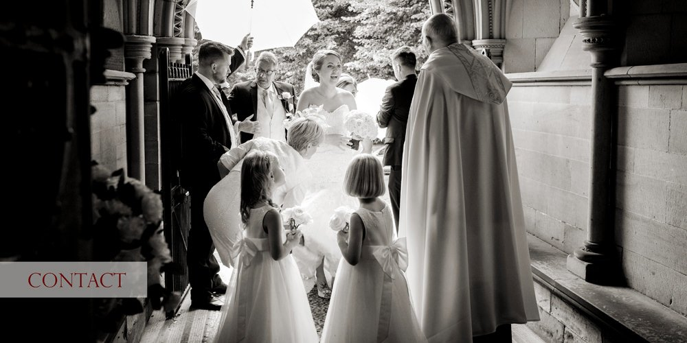 A bride arrives at Wentworth Church near Sheffield and Rotherham and is greeted by the vicar. A wonderful church wedding followed by a wedding reception at Wentworth Woodhouse. A black and white photograph by Sheffield wedding photographer John Mottershaw.