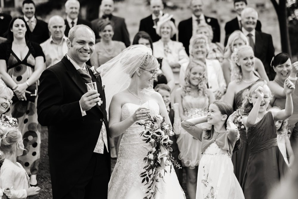 informal wedding photography at Tankersley Manor near Sheffield. Girl smiles at the bride.
