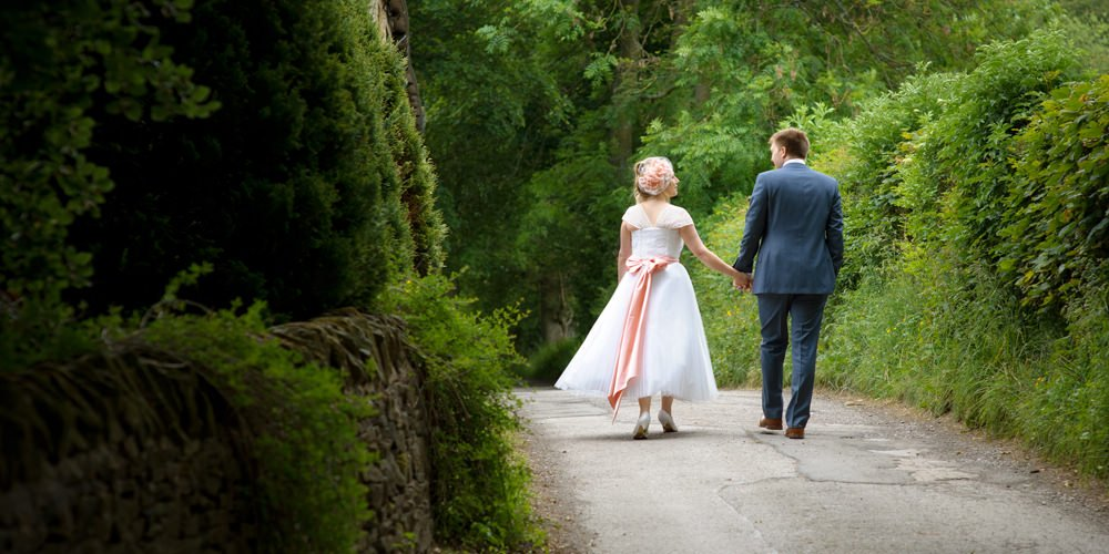 A bride and groom walk along the lane near Losehill House in the Derbyshire Peak District after their wedding. Natural wedding photography by Sheffield wedding photographer John Mottershaw.