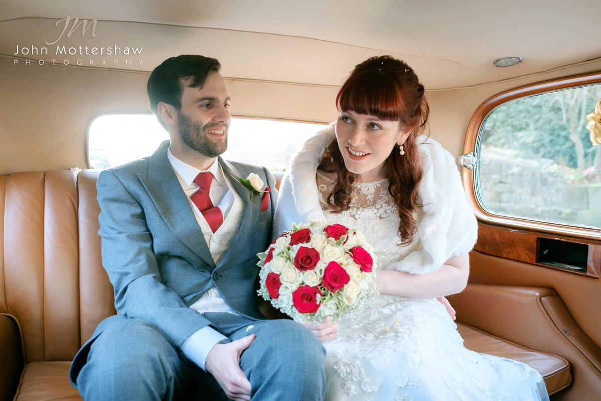 Wedding photograph of a bride and groom in the back of a vintage Rolls Royce.