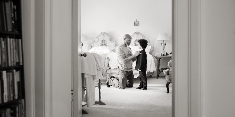A preparation photograph showing a father helping his young son to get ready for the church wedding. Documentary wedding photography by Sheffield wedding photographer John Mottershaw.