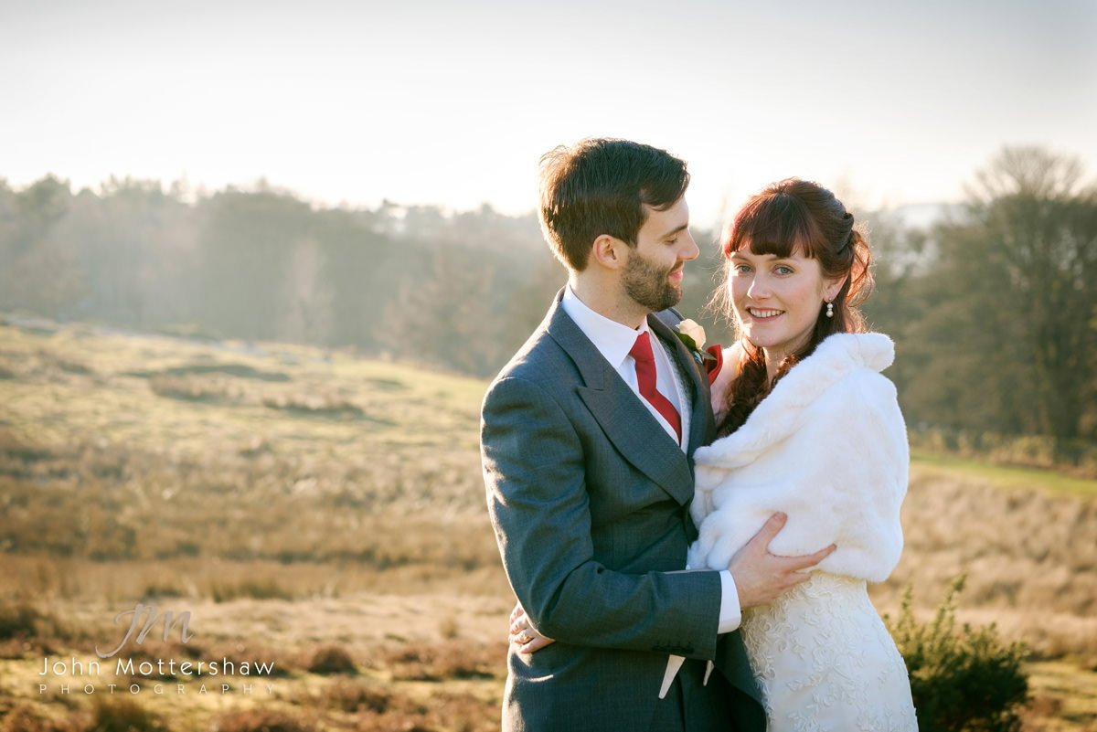 Wedding photograph of a bride and groom on the moors above Sheffield in winter sunshine. Wedding photography by John Mottershaw.