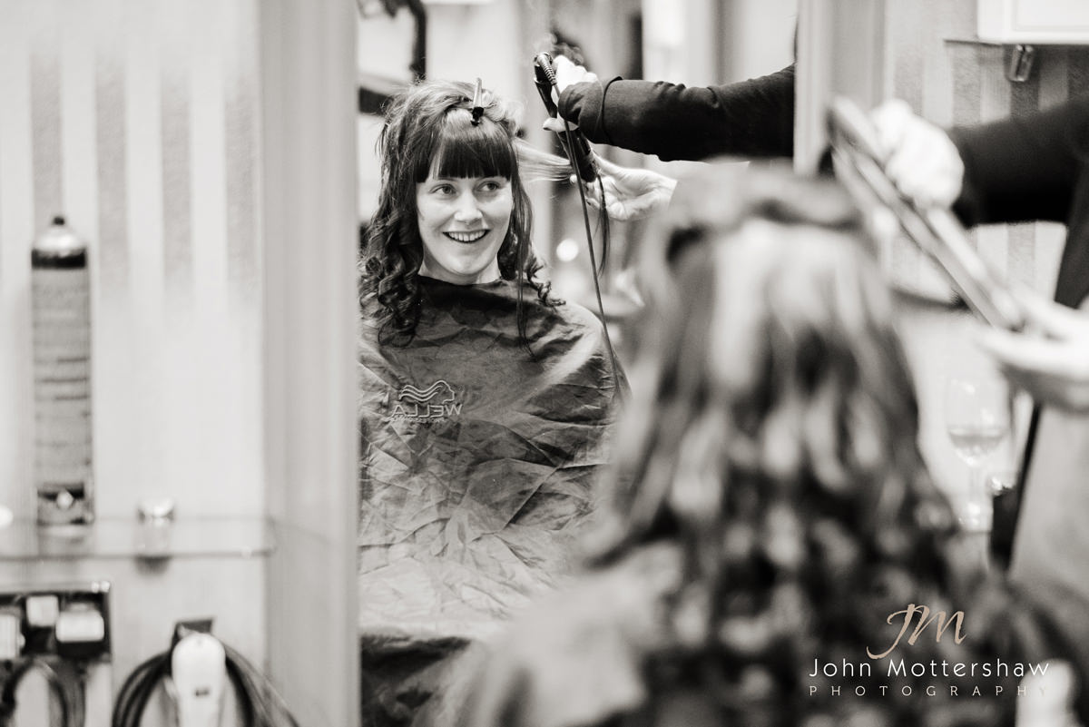 Black and white wedding photograph of the bride at the hairdressers before a wedding at St. Anne's Church in Buxton
