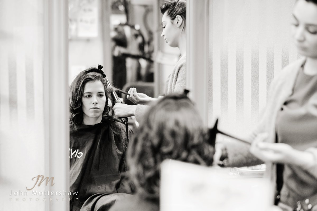 Black and white wedding photograph of a bridesmaid looking in the mirror at the hairdressers before a wedding at St. Anne's Church in Buxton