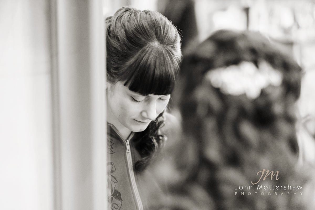 Black and white wedding photograph of the bride looking in the mirror at the hairdressers before a wedding at St. Anne's Church in Buxton