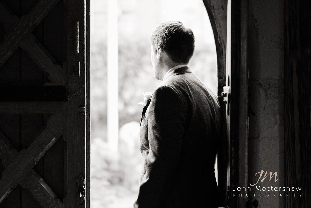 Black and white wedding photograph of an usher awaiting the arrival of the bride at Saint Anne's Church in Buxton