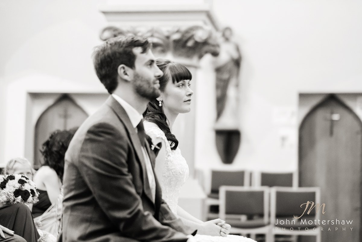 Black and white wedding photograph of a couple listening to a reading at Saint Anne's Church in Buxton.
