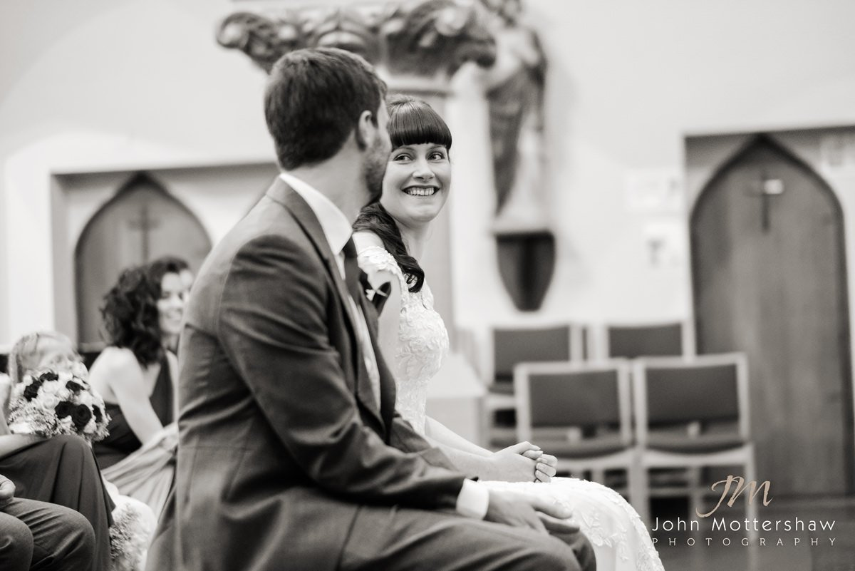 Black and white wedding photograph of the bride looking at her groom during the wedding ceremony at Saint Anne's Church near Buxton. Photography by Sheffield wedding photographer John Mottershaw.