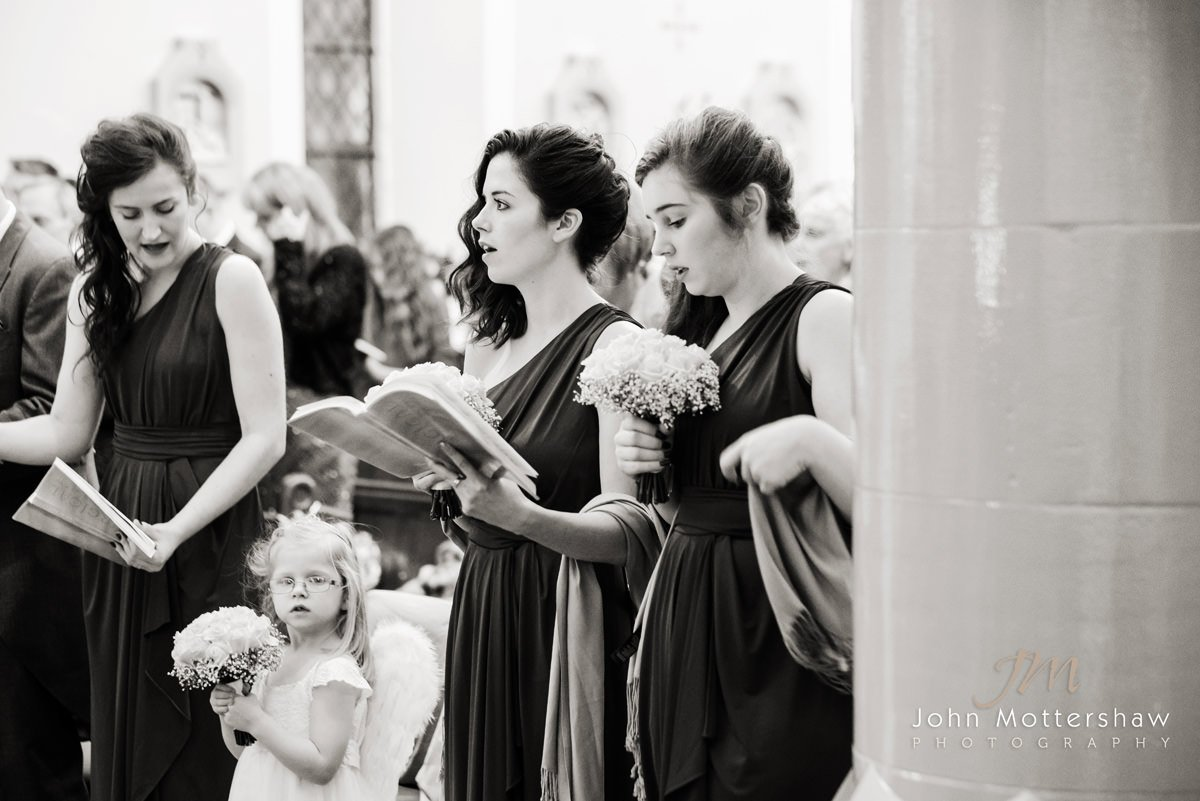Black and white wedding photograph of the bridesmaids singing a hymn during the wedding ceremony at Saint Anne's Church near Buxton. Photography by Sheffield wedding photographer John Mottershaw.