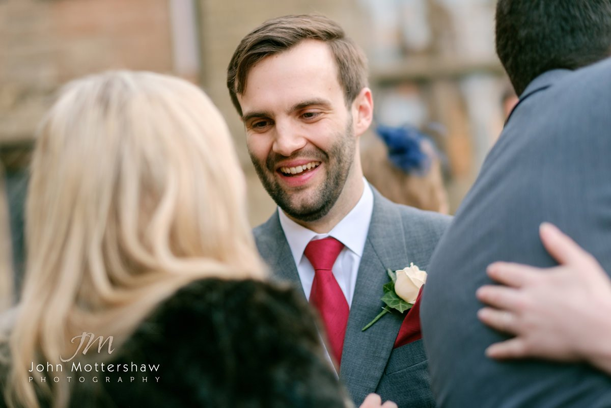 Informal wedding photograph outside Saint Anne's Church in Buxton of the groom laughing with a guest. Wedding photography by Sheffield wedding photographer John Mottershaw.