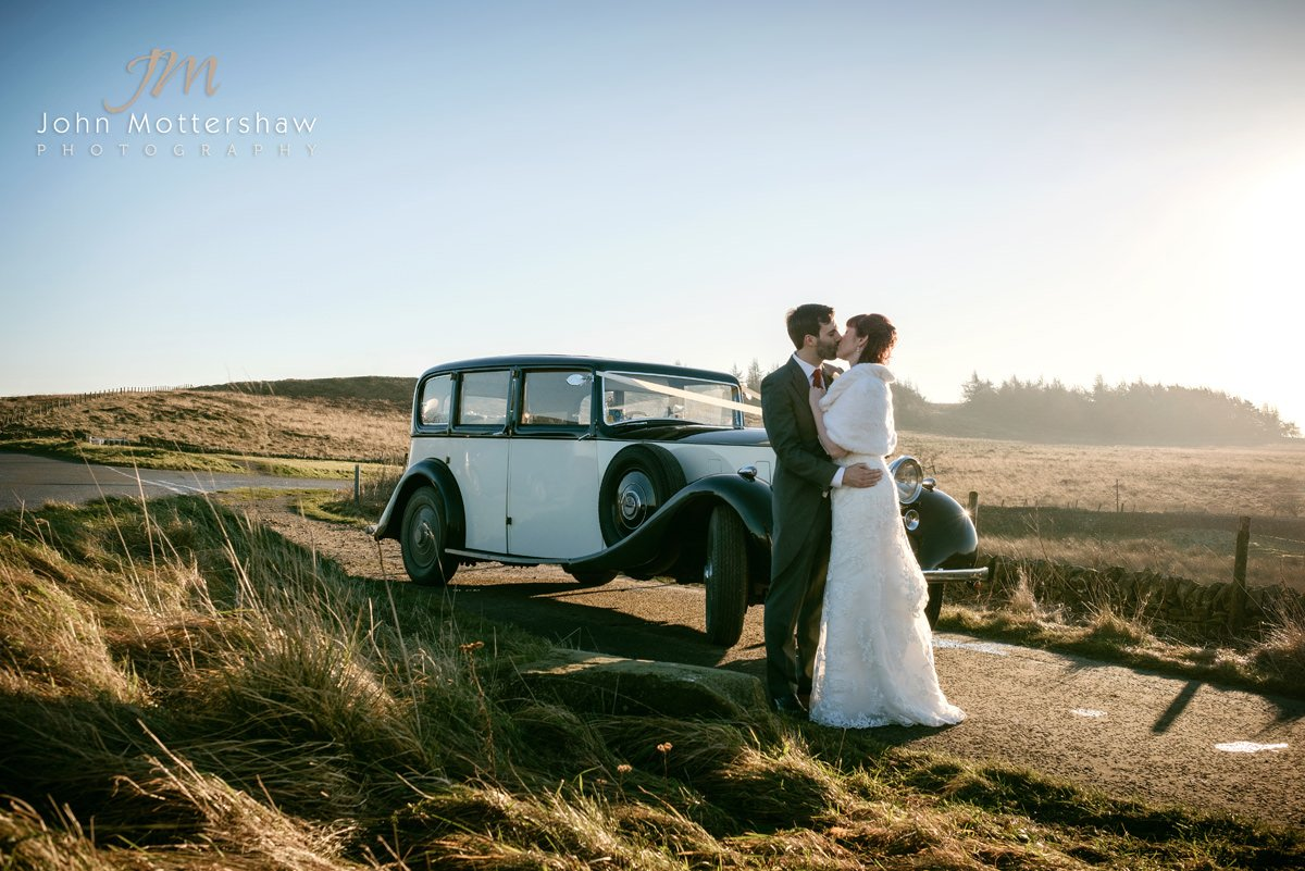 wedding photography near Sheffield of a bride and groom holding each other and enjoying the moment in front of a Rolls Royce Phantom. Image was taken on the moors above the Maynard by Sheffield wedding photographer John Mottershaw.
