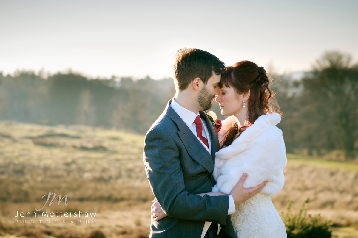 wedding photography near Sheffield of a bride and groom holding each other and enjoying the moment. Image was taken on the moors above the Maynard by Sheffield wedding photographer John Mottershaw.