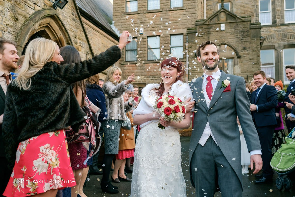 Wedding photograph of confetti, with the bride laughing, taken outside Saint Anne's Church, Buxton.