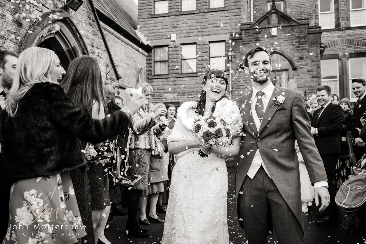 Black and white wedding photograph of confetti outside Saint Anne's Church, Buxton.