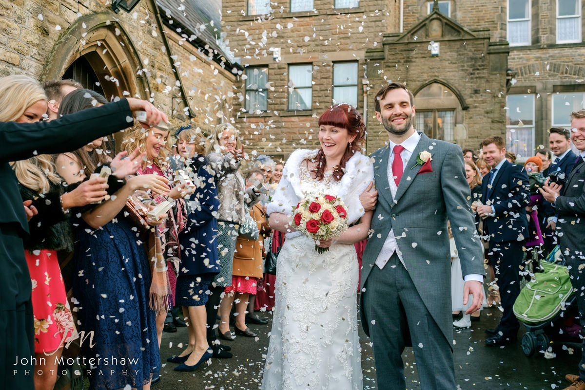 wedding photography in Buxton. A lively confetti shot outside Saint Anne's Church in Buxton.